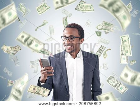 Portrait of a young smiling African American businessman wearing a suit and a shirt and looking at his smartphone screen. Gray background a dollar rain