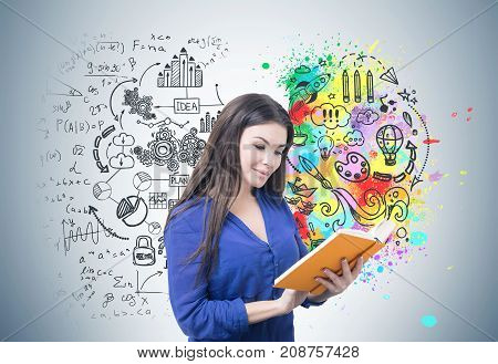 Portrait of a young smiling businesswoman wearing a blue blouse and reading an orange book. Gray background with a stylized colorful brain sketch