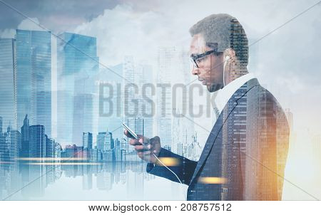 Side view of a young African American businessman holding a smartphone and wearing glasses. A morning cityscape panorama. Toned image double exposure mock up