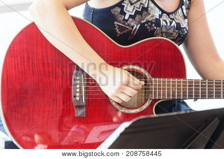 A young woman Playing a Red Guitar