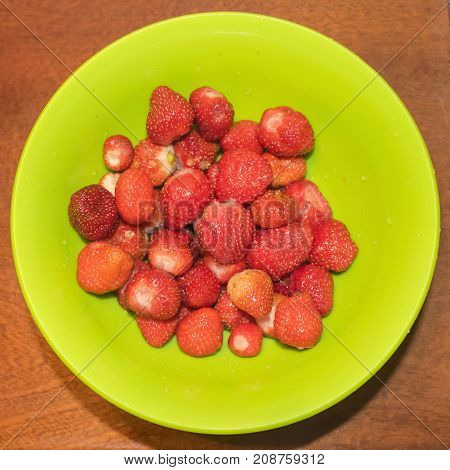 Fresh strawberry on a green plate top view
