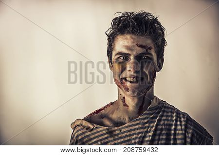 Male zombie standing on dark background, smiling to the camera