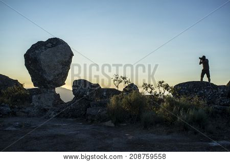 Silhouette of a photographer shooting sun rising above the mountain. Montanchez Famous megalithic monument Caceres Spain
