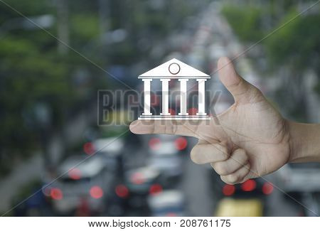 Bank icon on finger over blur of rush hour with cars and road Business banking online concept