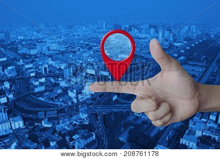 Map pin location button on finger over modern city tower street and expressway Map pointer navigation concept