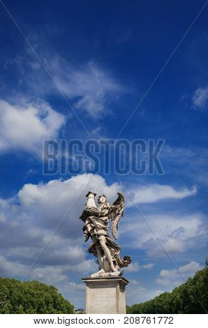 Angel statue looks at the heavenly sky. A 17th century baroque masterpiece at the top of Holy Angel Bridge balustrade in the center of Rome