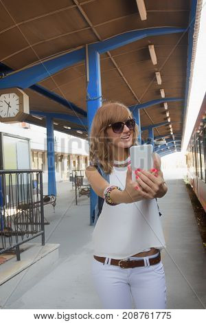 Cute young girl using cellphone on a retro railway station.