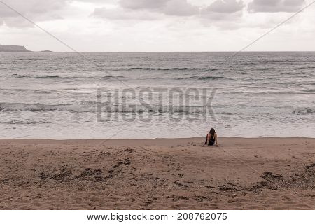 Woman staring at the sea with her back facing the camera
