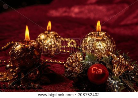 Christmas still life with three spherical candles on Burgundy background