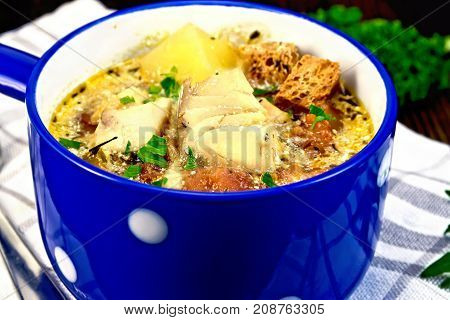 Fish soup with tomatoes, potatoes, peppers, croutons and cream in a blue bowl on a towel, parsley on a wooden board background
