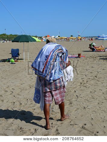Abusive Street Vendor With Towels On The Beach