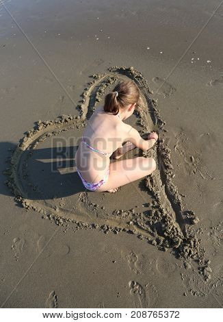 Little Girl With Bathing Suit Draws A Heart On The Wet Sand Of T