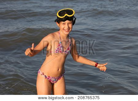 Little Girl With Diving Mask Plays And Dives At The Sea In Summe
