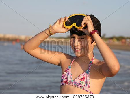 Little Girl With Diving Mask Plays And Dives At The Sea
