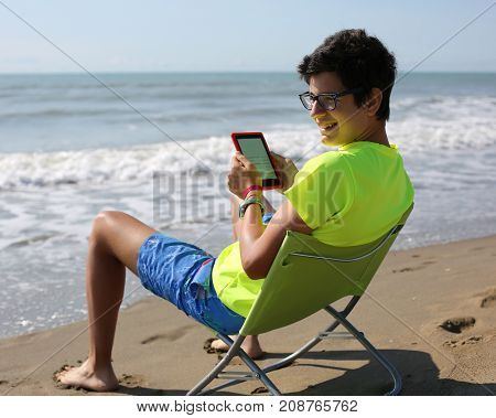 Smiling Caucasian Boy Reads An Ebook Sitting On The Beach Chair
