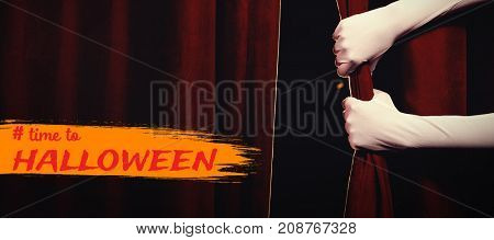 Graphic image of time to Halloween text against cropped hands in gloves holding curtain at stage