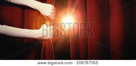Cropped hands in white gloves holding curtain at illuminated stage