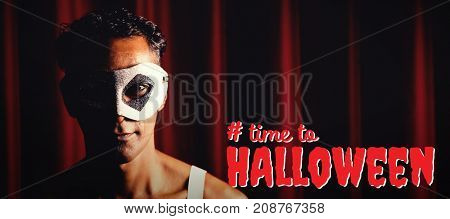 Digital composite image of time to Halloween text against portrait of man in masquerade mask