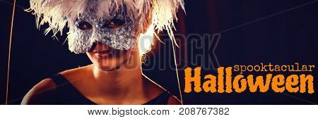 Graphic image of spooktacular Halloween text against portrait of woman in masquerade mask and wig