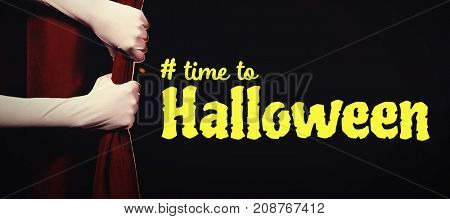 Digital image of time to Halloween text against cropped hands in gloves holding curtain at stage