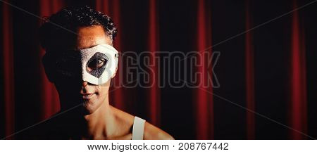 Portrait of man in masquerade mask at stage