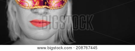 Close-up portrait of woman in masquerade mask against black background