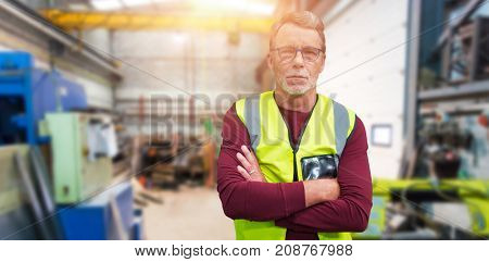 Portrait of senior worker wit arms crossed wearing reflective clothing against workshop