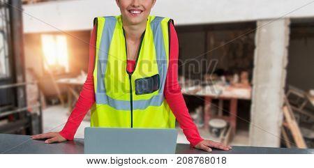 Portrait of confident female architect wearing reflective clothing against workshop