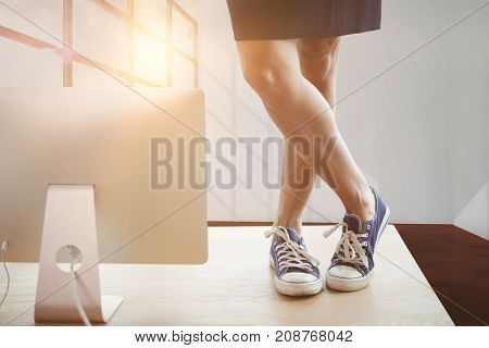 Low section of businesswoman standing on table by computer against interior of empty room