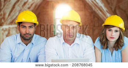Portrait of architects wearing hardhats while sitting at table against room in house under construction