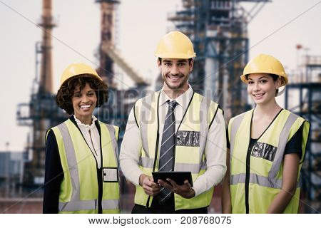 Portrait of architects in reflective clothing holding tablet computer against image of factory