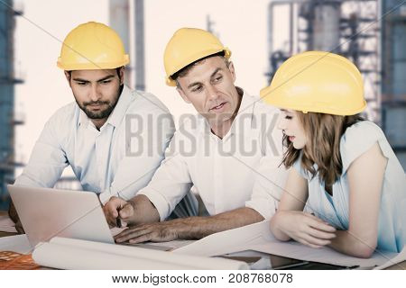 Architects discussing while sitting at table against view of industry