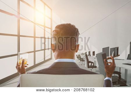 Rear view of businessman holding whisky glass and cigar against computers in empty office