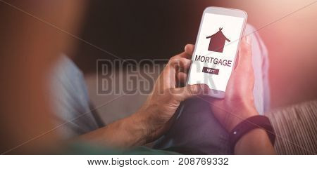 Graphic image of mortgage text with icon against man using mobile phone in living room