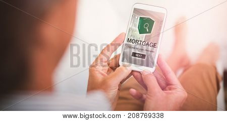 Digital image of mortgage text with icon and bedroom against man using mobile phone in living room