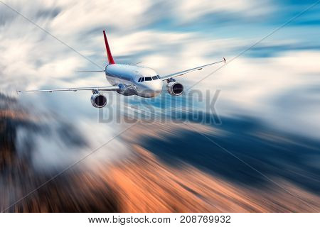 Airplane with motion blur effect. Landscape with flying passenger airplane and blurred background with sky with low clouds, orange forest at sunset. Passenger airplane is landing. Commercial aircraft