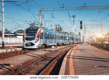 High speed train arrives on the railway station at sunset in Europe. Modern intercity train on the railway platform. Industrial landscape with passenger train on railroad. Railway transportation