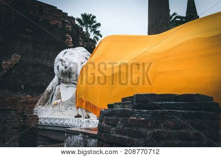 Ayutthaya Thailand - October 13 2017: Old anceint buddha statue with yellow robe sleep at Wat Yai Chaimongkol Ayutthaya Thailand.