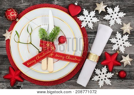 Merry christmas ribbon and table place setting with plates, napkin, cutlery and fir with bauble decorations on red mat on rustic wood background.