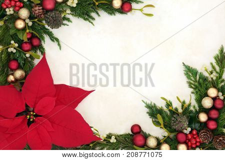 Christmas border with poinsettia flower with red and gold bauble decorations, holly, mistletoe, ivy, fir and pine cones on parchment paper.
