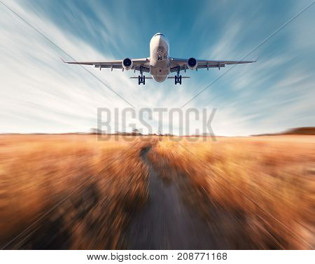 Airplane with motion blur effect. Landscape with flying passenger airplane and blurred blue sky with clouds, orange grass field with trail at sunset. Passenger airplane is landing. Commercial aircraft