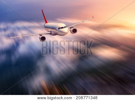 Modern airplane mith motion blur effect is flying over low clouds at sunset. Landscape with passenger airplane, blurred clouds, sunlight in dusk. Passenger aircraft. Business travel. Commercial plane