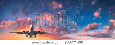 Airplane and beautiful sky. Landscape with passenger airplane is flying in the blue sky with red, purple and orange clouds at sunset. Travel. Passenger airliner. Commercial aircraft. Private jet