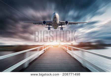 Airplane in motion with blurred background. Landscape with passenger airplane is flying over the wooden bridge against overcast sky at sunset. Journey. Passenger airliner is landing. Commercial plane