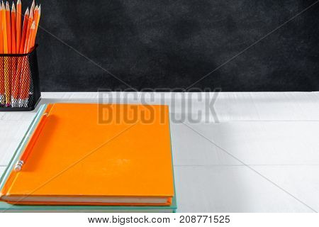 book and pencil on white table black board background with study and education concept.selective focus