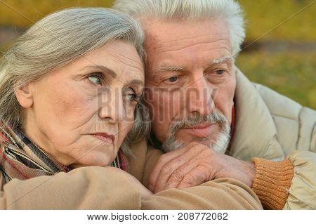 Portrait of sad senior couple in autumn park