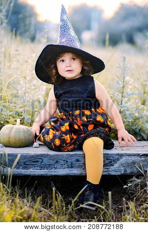 Toddler girl ready for halloween and trick or treat. Adorable little witch. Toned in blue and yellow.