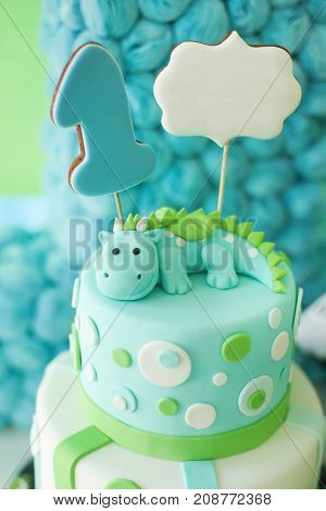 Blue and green first year birthday cake with cute dragon for little boy. Vertical photo.