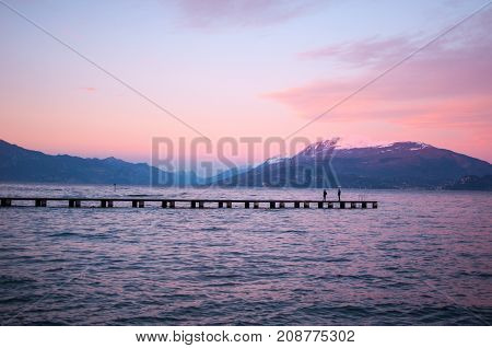 Romantic violet sunset on a lake with a long pier and a couple strolling by