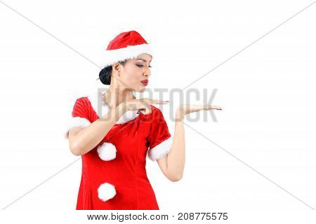 Christmas concept : Beautiful Asian woman in Santa Claus clothes and hat opening her hand and pointing finger for concept placing a sign or object isolated on white background